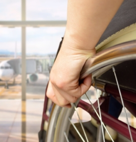 Close up of a hand on a wheel of a manual wheelchair. In the background is an airplane on a tarmac.