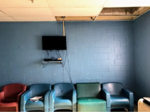 A room with brick walls with chairs and a television
