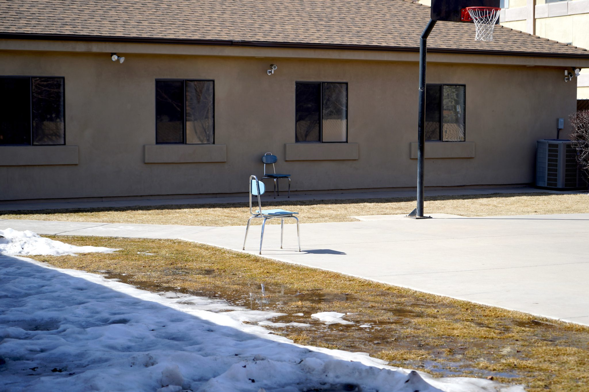 Lone chair in a basketball court area with snow