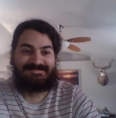 Spencer, a white male in his 20s with a long brown beard smiles for the camera